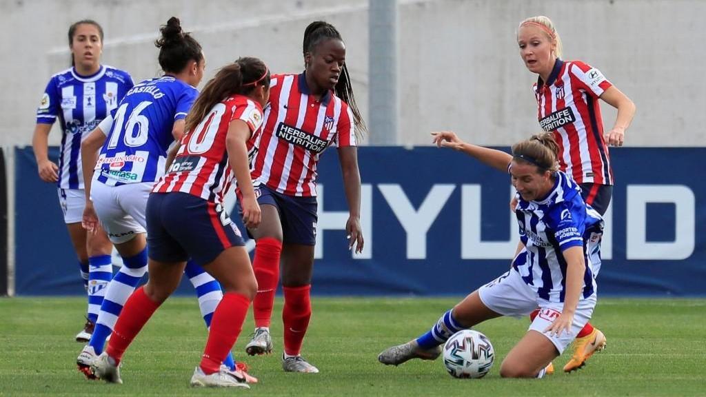 Las jugadoras del Atlético de Madrid buscan robar un balón a Jenni...