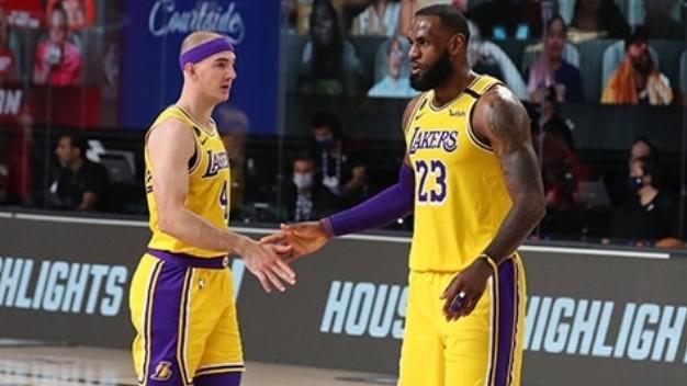 Alex Caruso choca la mano a LeBron James durante un partido de los...