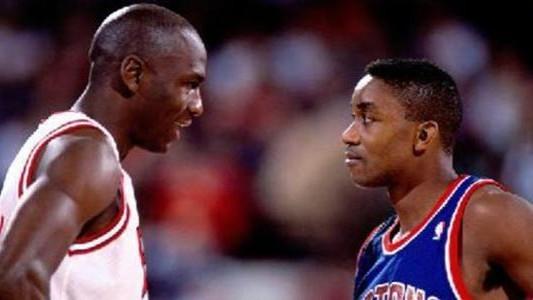 Michael Jordan habla con Isiah Thomas durante un partido.
