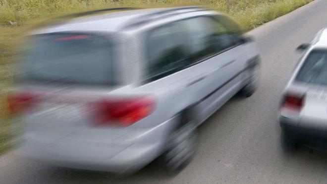 Un monovolumen adelanta a otro turismo en una carretera convencional.