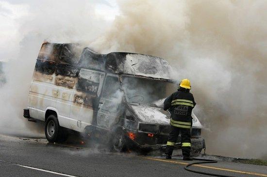 Un bombero intenta extinguir el fuego de una furgoneta incendiada.
