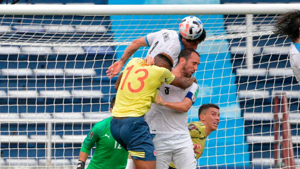 Colombias Yerry Mina (L) and Uruguays Jose Maria lt;HIT gt;Gimenez lt;/HIT gt; (top) and Diego Godin jump for the ball during their closed-door 2022 FIFA World Cup South American qualifier football match at the Metropolitan Stadium in Barranquilla, Colombia, on November 13, 2020, amid the COVID-19 novel coronavirus pandemic. (Photo by Raul ARBOLEDA / AFP)