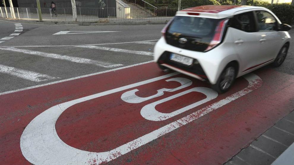 Un coche circula por una calle de Barcelona con la velocidad limitada a 30 km/h.
