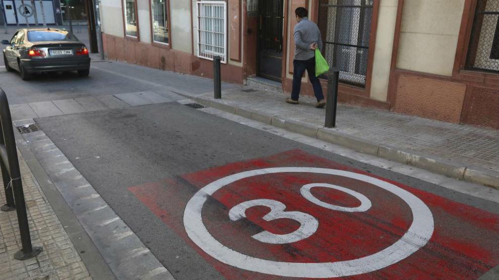 Un coche y un peatón en una calle de Barcelona con la velocidad limitada a 30 km/h. Foto: Antonio Moreno.
