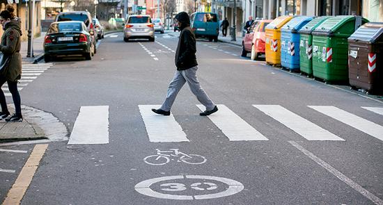 Un peatón cruza una calle con la velocidad limitada a 30 km/h.