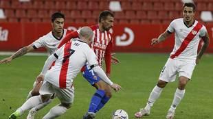 Aitor García controla el balón entre los rayistas Velázquez, Isi y...