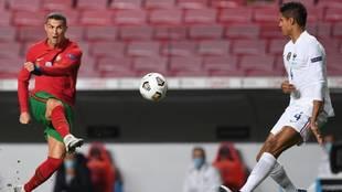Varane trata de interceptar un disparo de Cristiano en el...