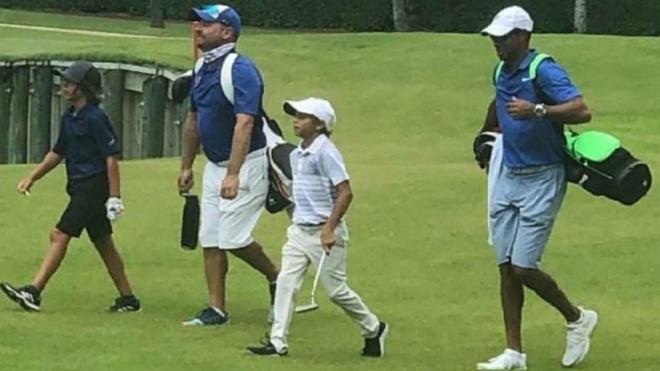 Tiger Woods ejerciendo de caddie de su hijo Charlie en un torneo...