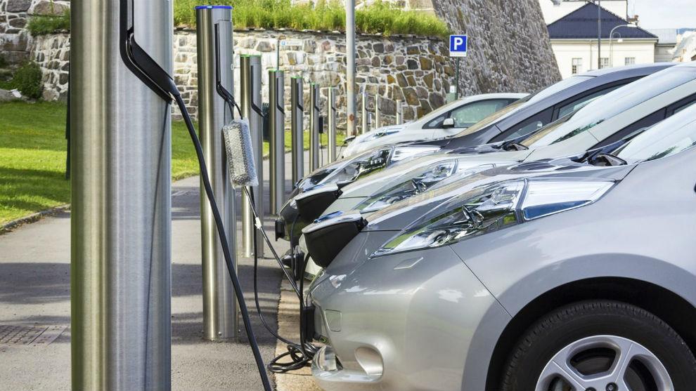 Varios coches enchufados a cargadores eléctricos.
