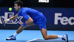 Djokovic intenta devolver una pelota de espaldas