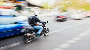 Un motorista circula por la derecha de una vía urbana.