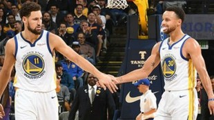 Klay Thompson y Stephen Curry chocan las manos durante un partido de...
