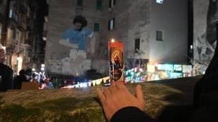 Un aficionado con una vela enfrente de uno de los murales de Maradona...