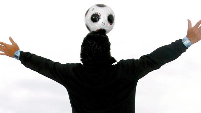 Diego Maradona juega con un balón mientras posa para los medios en el...