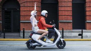 Dos jóvenes circulan en un scooter eléctrico Niu MQi+ Sport.