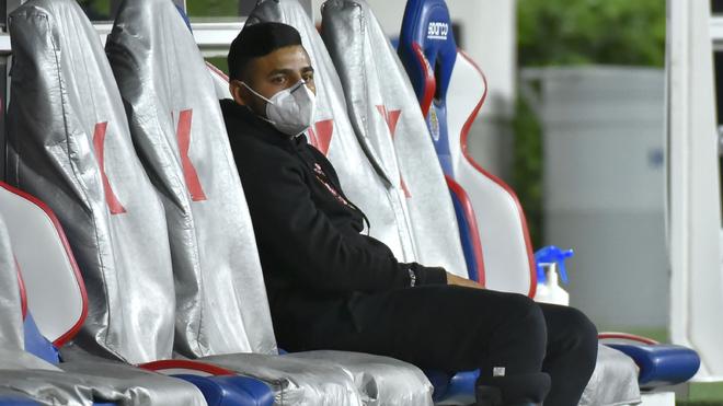 Alexis Vega lesionado en la banca del Estadio Akron.