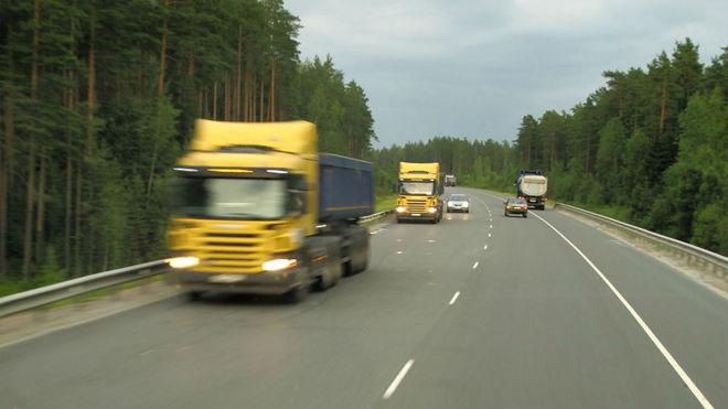 Varios camiones circulan por el arcén en una carretera de Grecia.