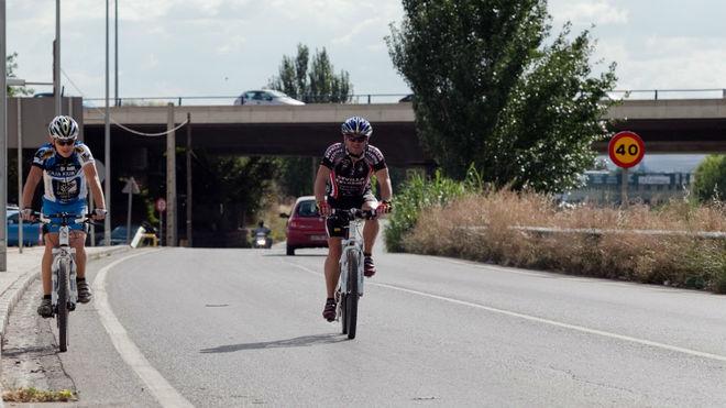 Dos ciclistas circulan por una carretera convencional de doble...