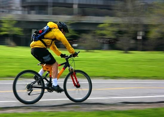 Un ciclista circula por el arcén de una carretera.