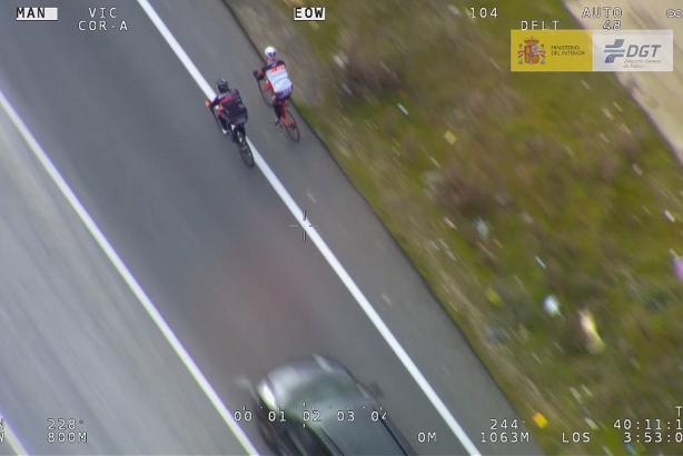 Dos ciclistas circulan en paralelo por una carretera convencional de doble sentido y con línea continua.