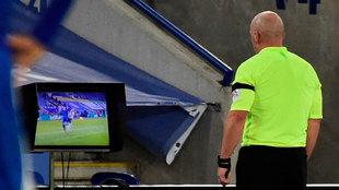 El colegiado inglés Simon Hooper chequea el VAR durante un partido