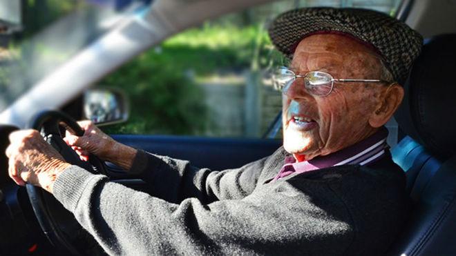Un anciano conduce su vehículo.