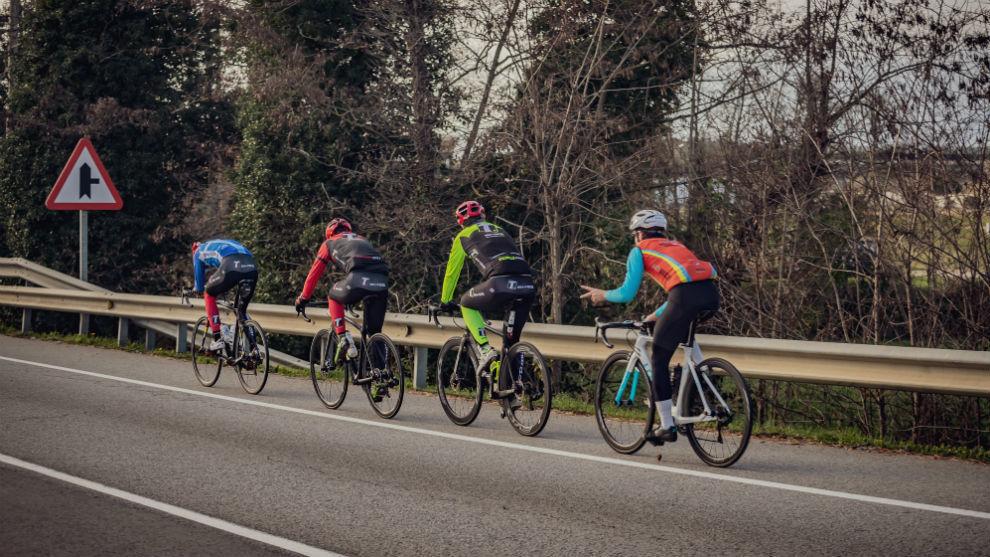 Varios ciclistas circulan en hilera por el arcén de una carretera convencional.