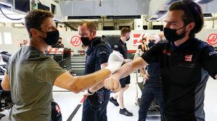 Romain Grosjean choca el puño vendado con uno de los mecánicos de...