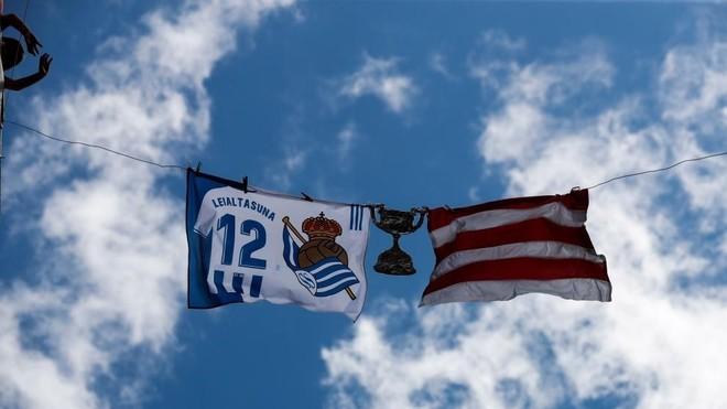 Una bandera de Real Sociedad y otra del Athletic, junto a una Copa,...