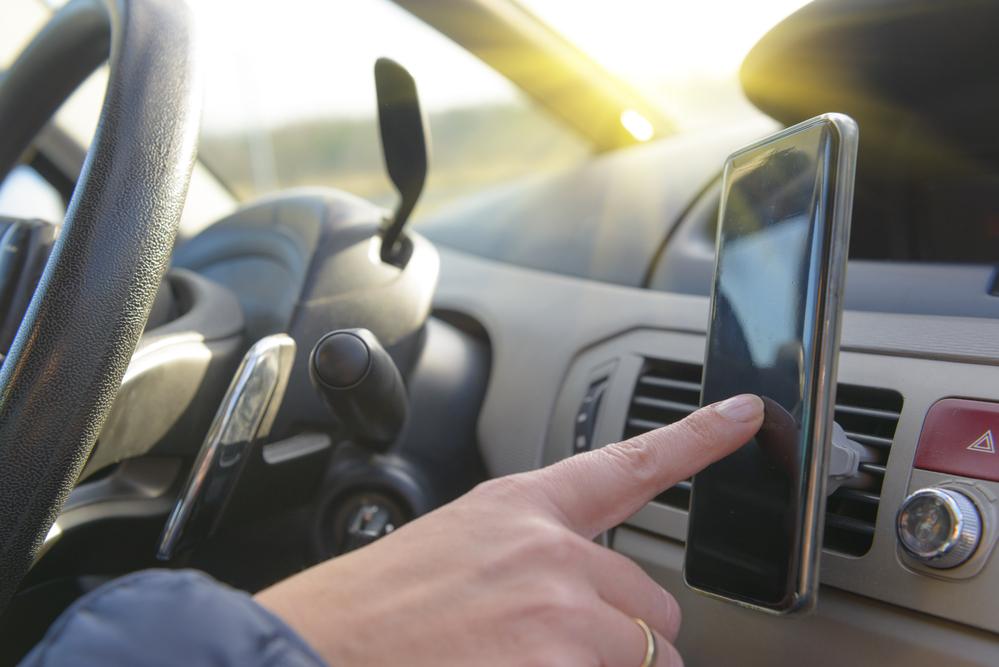Un conductor usa el teléfono móvil anclado con un soporte al salpicadero.