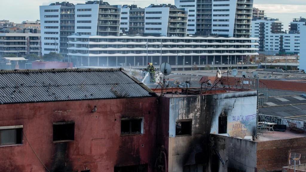 Los bomberos trabajan en la nave que ardió en Badalona.