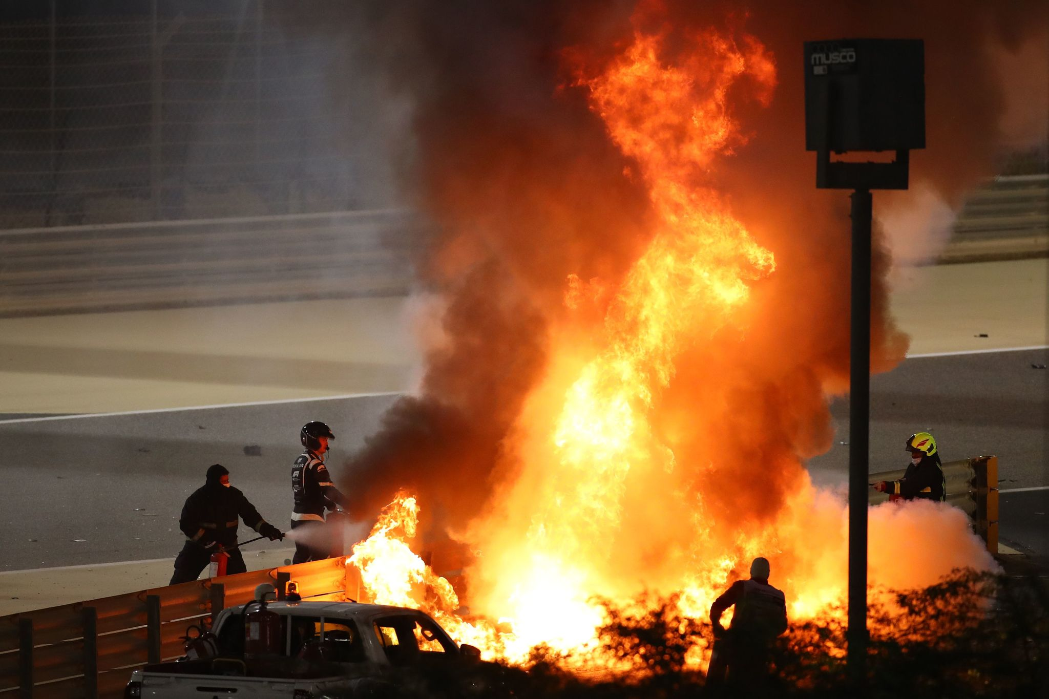 TOPSHOT - Fire marshals put out a fire on Haas F1s French driver Romain lt;HIT gt;Grosjean lt;/HIT gt;s car during the Bahrain Formula One Grand Prix at the Bahrain International Circuit in the city of Sakhir on November 29, 2020. (Photo by Bryn Lennon / POOL / AFP)