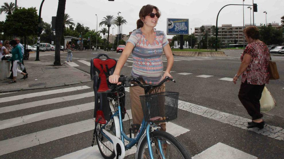 Una ciclista cruza a pie por un paso de peatones.