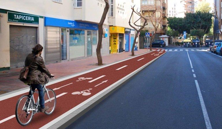 Un ciclista circula por una acera-bici, una vía ciclista señalizada sobre la acera.