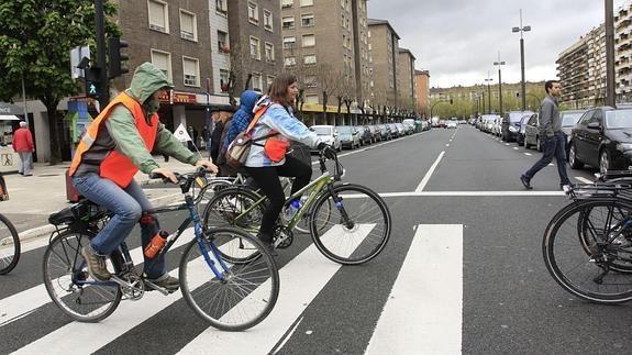 Varios ciclistas cruzan por un paso de cebra sin bajarse de la bici.