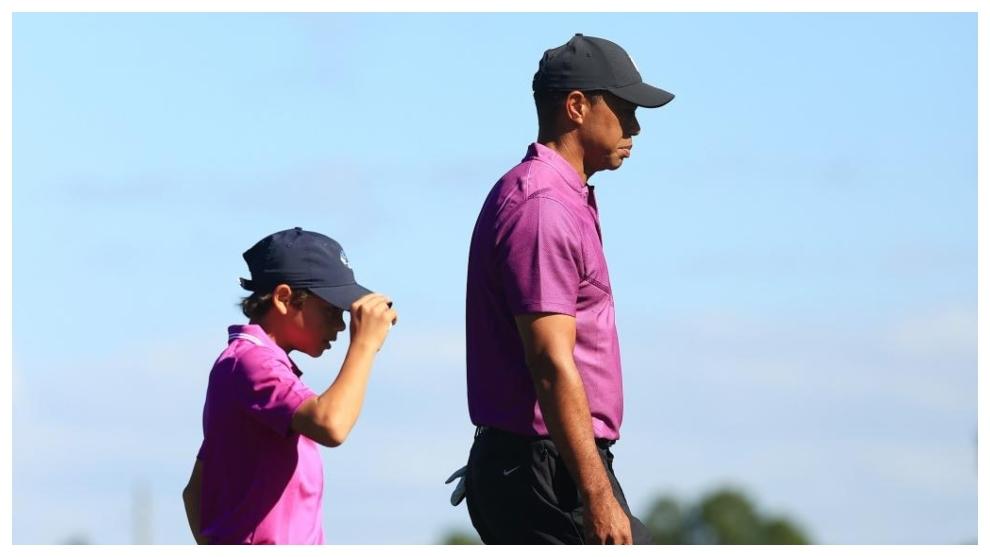 Tiger Woods camina con su hijo Charlie, detrás.