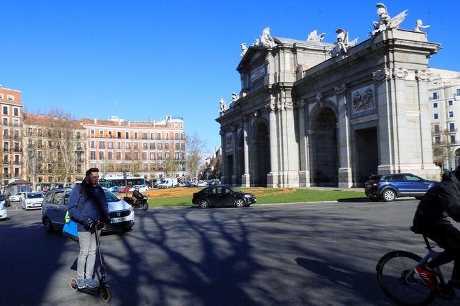 Un hombre en patinete delante de la Puerta de Alcalá en Madrid.