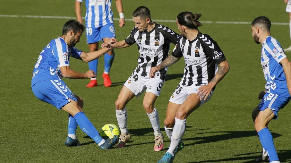 Aitor Sanz y Fidalgo luchan por hacerse con el balón ante la presencia de Marc Mateu