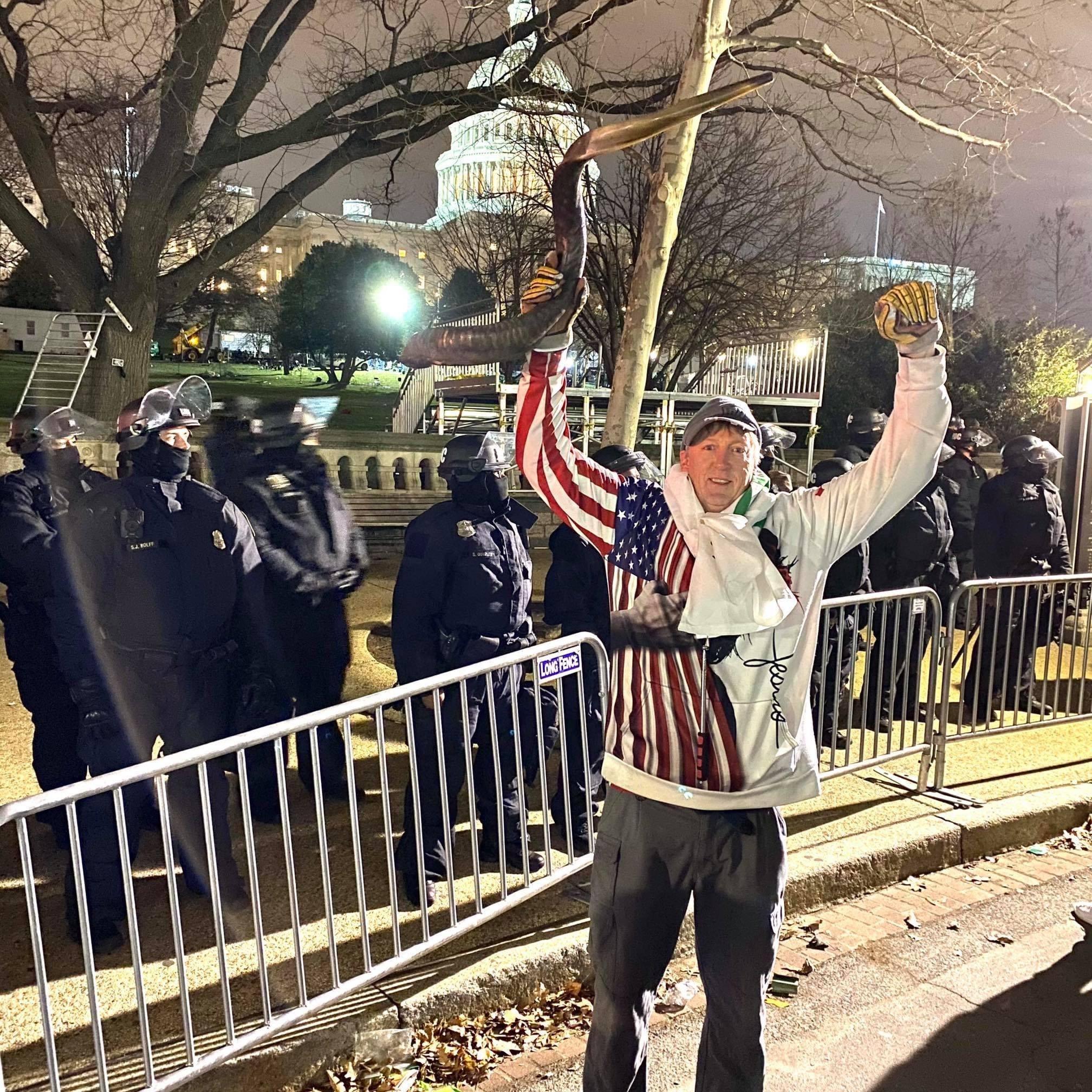 Wood posa eufórico brazos en alto junto a la policía con el Capitolio al fondo.