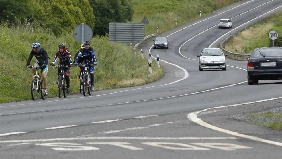 Tres ciclistas circulan por una carretera convencional.