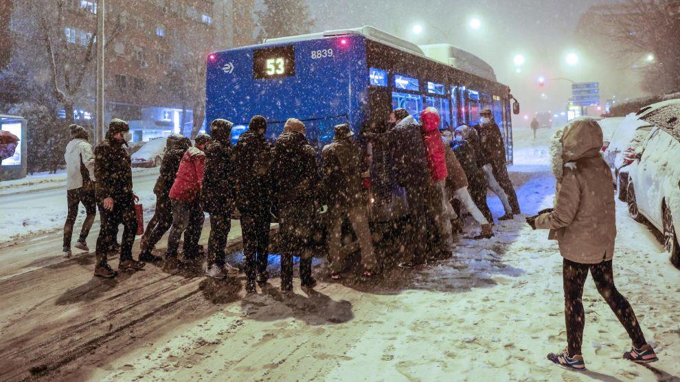 Several people pushing bus