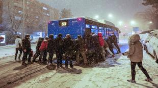 Varias personas empujan un autobús bajo una intensa nevada en la...
