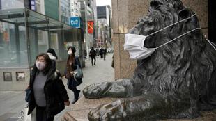 Una persona pasa con mascarilla junto a la entrada de una tienda en el...