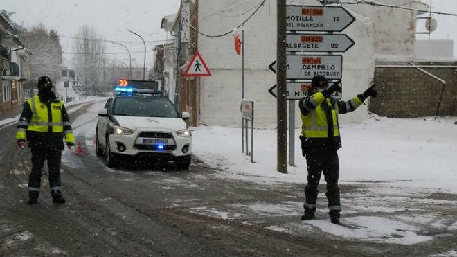 Dos agentes de la Guardia Civil controlan el tráfico en plena nevada.