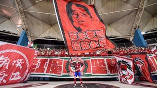 Ivo, capitán del Henan Jianye, ondea una bandera delante de los...