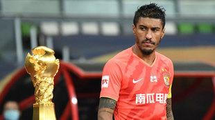 Paulinho mira el trofeo de la Superliga china mientras salta al campo...