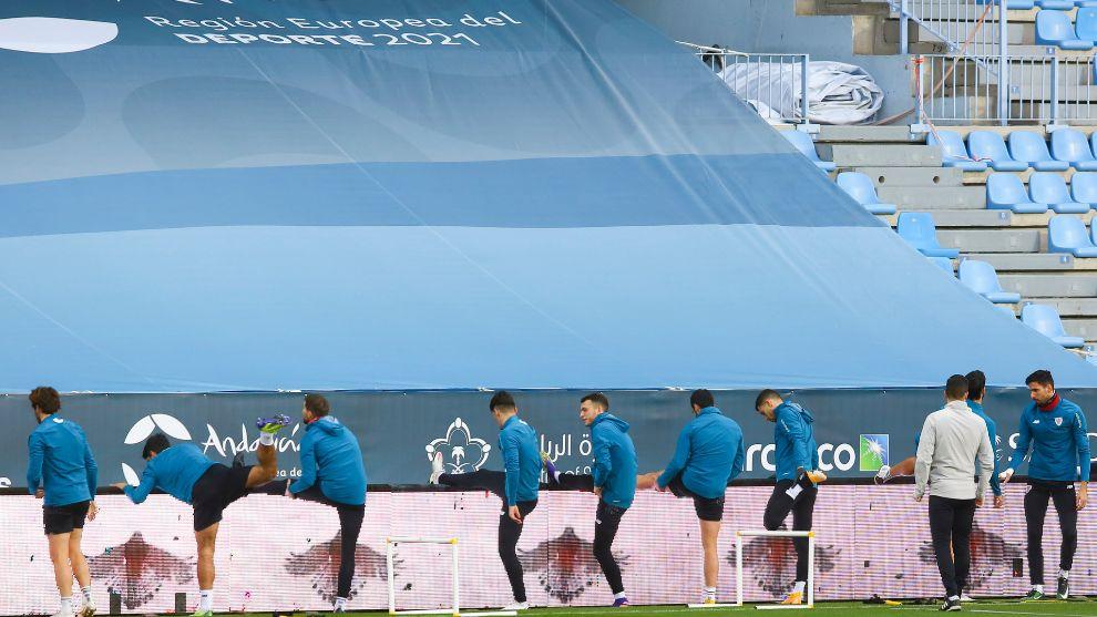 Los jugadores del Athletic estiran tras un ejercicio en el...