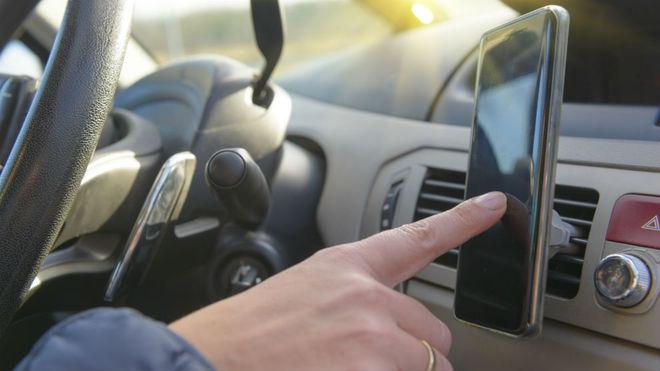 Un conductor manipula el teléfono móvil mientras conduce.