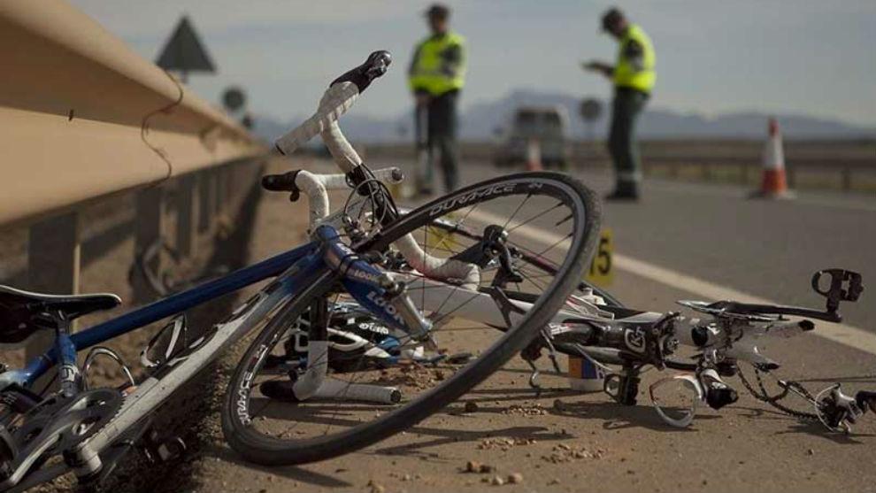 Dos guardias civiles recaban pruebas en el escenario de un atropello a dos ciclistas.