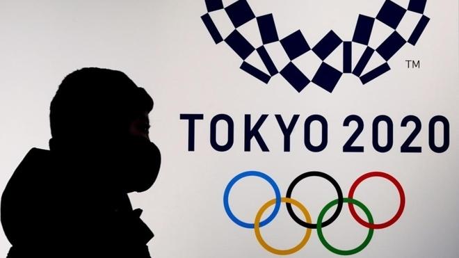 Una persona con mascarilla pasa delante del eslogan de Tokio 2020.